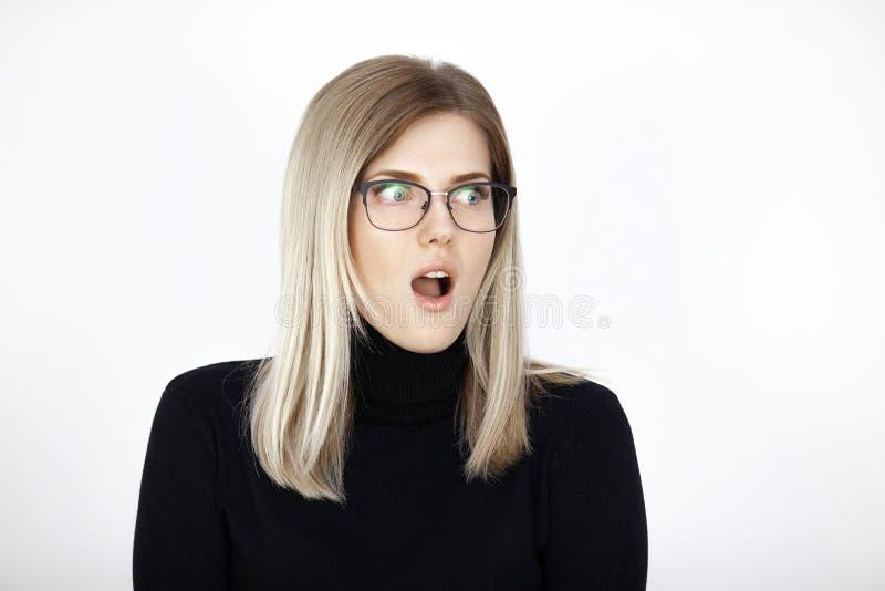 Den unga attraktiva blondinen förvånas extremt arkivfoto