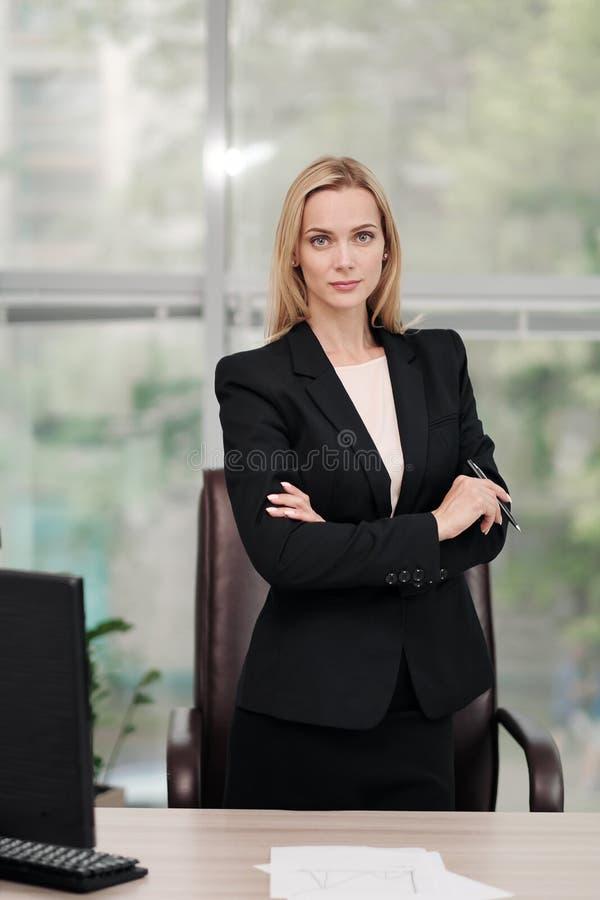 Den unga attraktiva Caucasian blonda kvinnan i svart affärsdräkt sitter på skrivbordet i ljust kontor Studera pappers- dokument arkivfoto