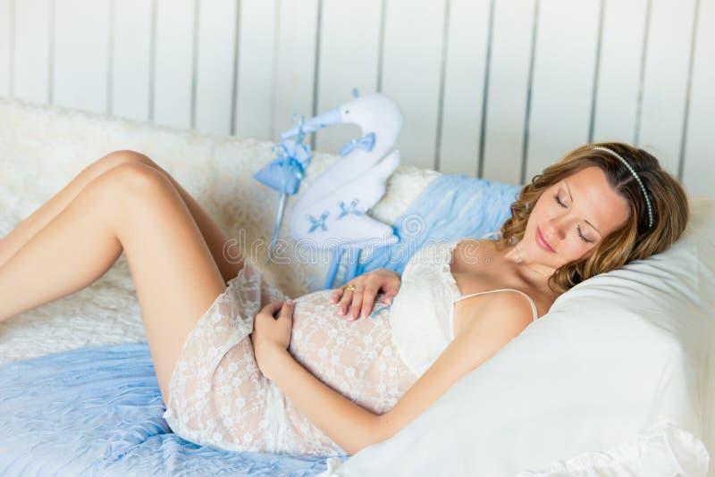 Den unga attraktiva gravida kvinnan med en härlig buk ligger på soffan med en leksakstork royaltyfri bild