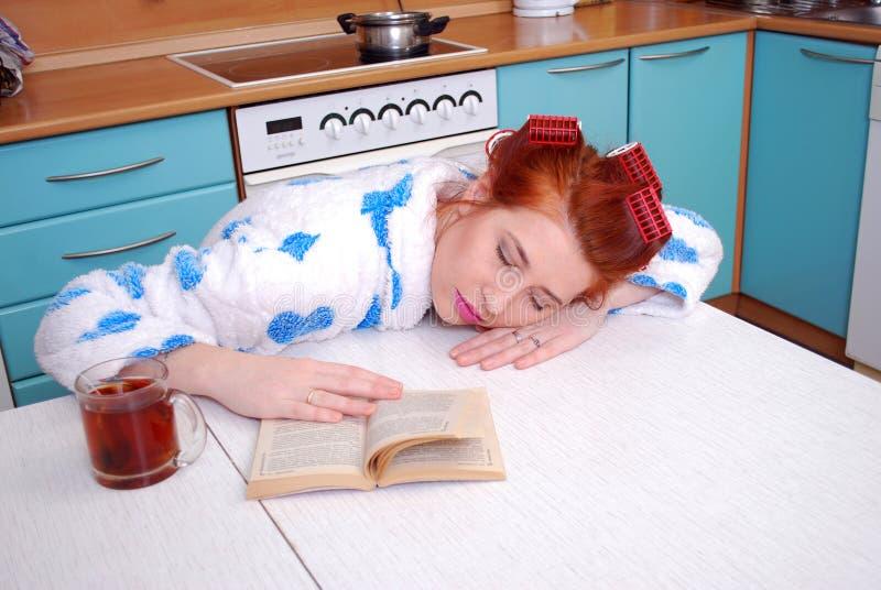 Den unga attraktiva hemmafrun har stupat sovande på ett köksbord som läser boken royaltyfria bilder