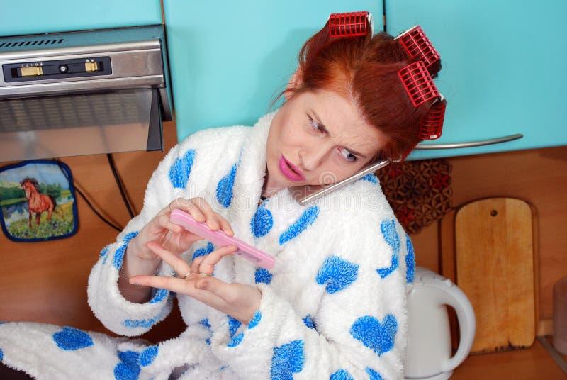 Den unga attraktiva hemmafrun i kök om papiljotter talar indignantly vid telefonen och gör manikyr arkivfoton