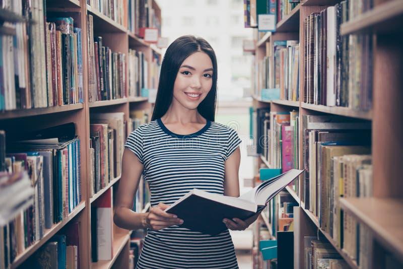 Den unga attraktiva klyftiga lyckade asiatiska kvinnliga studenten är holdien royaltyfri bild