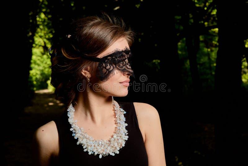 Den unga attraktiva kvinnan bär den sexiga genomskinliga svarta klänningen r royaltyfri fotografi