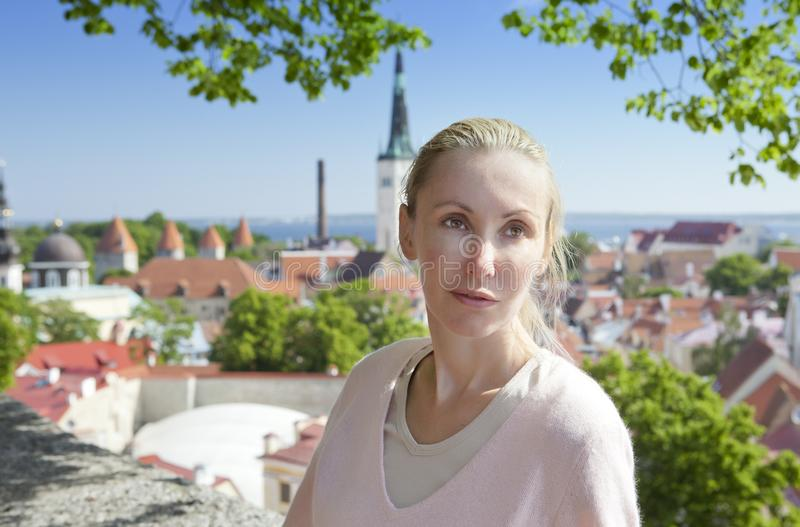 Den unga attraktiva kvinnan beundrar tak av hus av den gamla staden från ett observationsdäck tallinn estonia royaltyfri foto