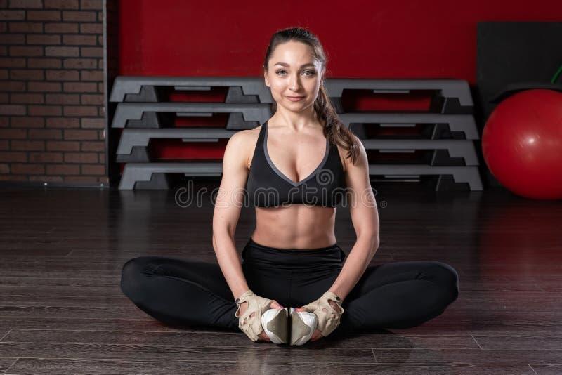 Den unga attraktiva kvinnan gör splittringcrossfit som sträcker med trxkonditionremmar i gym&en x27; s-studio arkivbilder