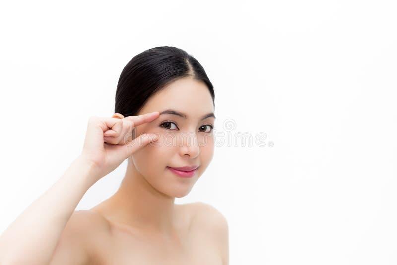 Den unga attraktiva kvinnan i det naturliga skönhetvillkoret som trycker på försiktigt, synar för att fokusera på eyecarehälsa royaltyfria foton