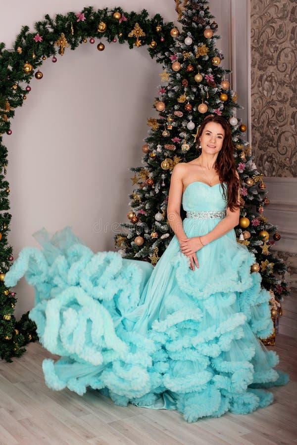 Den unga attraktiva kvinnan i en frodig blå klänning står nära trädet för det nya året royaltyfria bilder