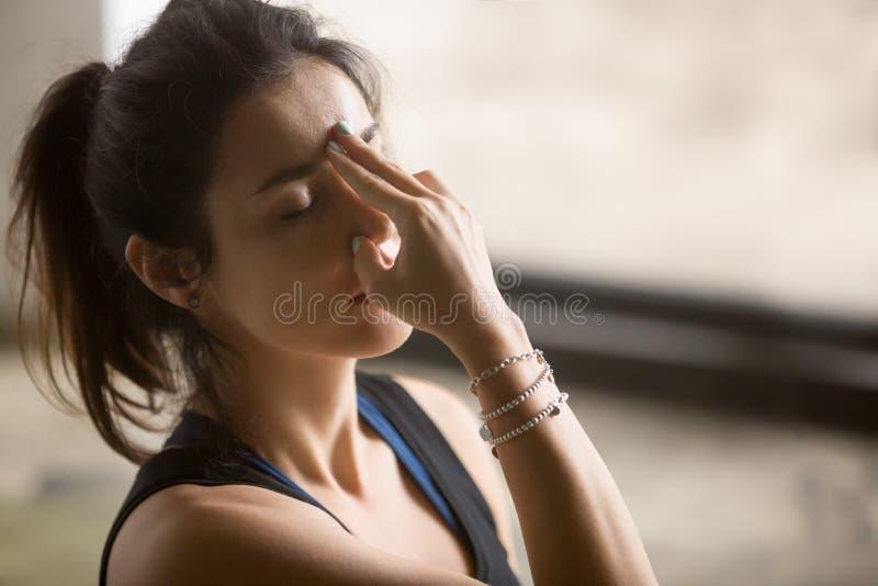 Den unga attraktiva kvinnan i nadishodhanapranayama poserar, studio b royaltyfri fotografi