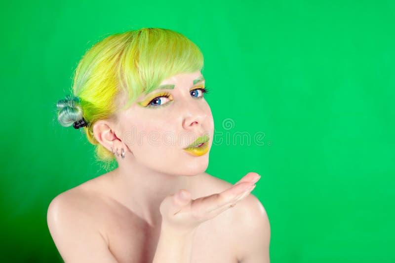 Den unga attraktiva kvinnan med grönt hår överför enkyss royaltyfria foton