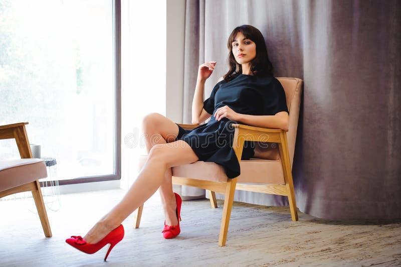 Den unga attraktiva kvinnan med långa ben i svart elegant klänning, sitter i stol nära fönster i inre av rum royaltyfri bild