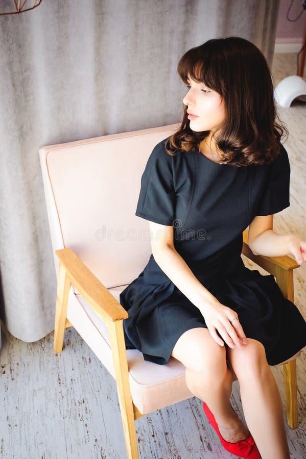 Den unga attraktiva kvinnan med långa ben i svart elegant klänning, sitter i stol nära fönster i inre av rum royaltyfria bilder