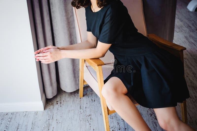 Den unga attraktiva kvinnan med långa ben i svart elegant klänning, sitter i stol nära fönster i inre av rum arkivfoton