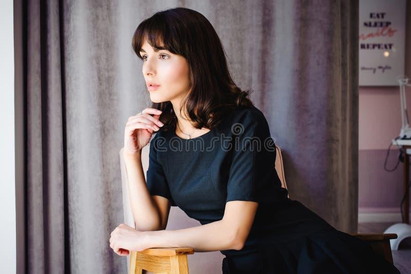 Den unga attraktiva kvinnan med långa ben i svart elegant klänning, sitter i stol nära fönster i inre av rum royaltyfria foton