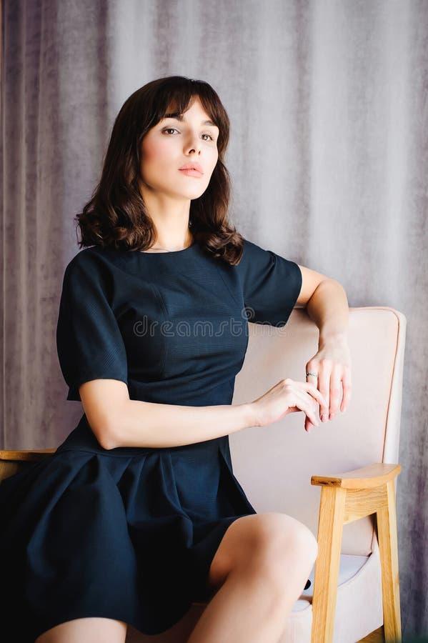 Den unga attraktiva kvinnan med långa ben i svart elegant klänning, sitter i stol nära fönster i inre av rum arkivfoto