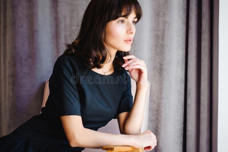 Den unga attraktiva kvinnan med långa ben i svart elegant klänning, sitter i stol nära fönster i inre av rum royaltyfri fotografi