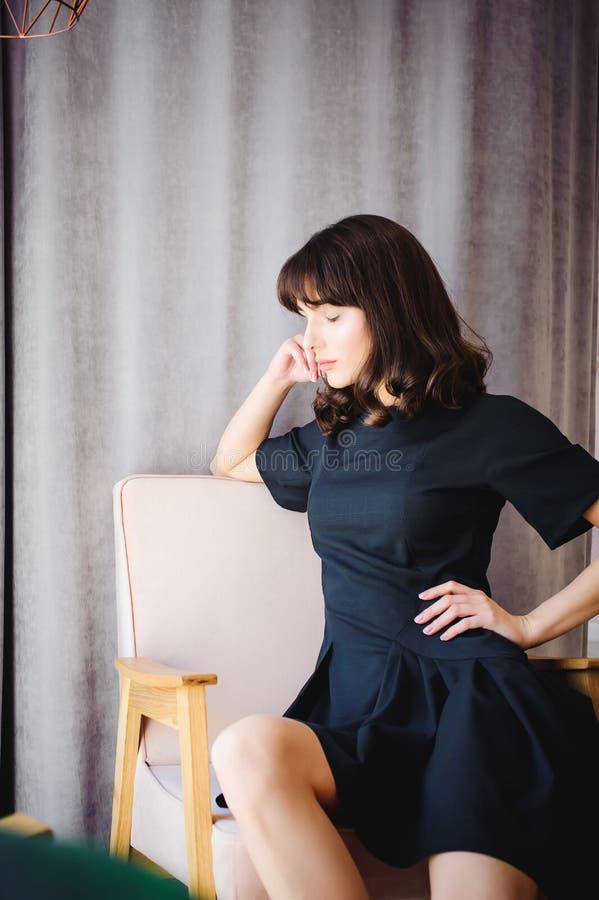 Den unga attraktiva kvinnan med långa ben i svart elegant klänning, sitter i stol nära fönster i inre av rum royaltyfri foto