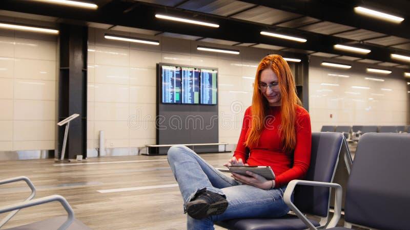 Den unga attraktiva kvinnan med rött hår och exponeringsglasbruksgrejen i flygplatsavvikelse är slö fotografering för bildbyråer