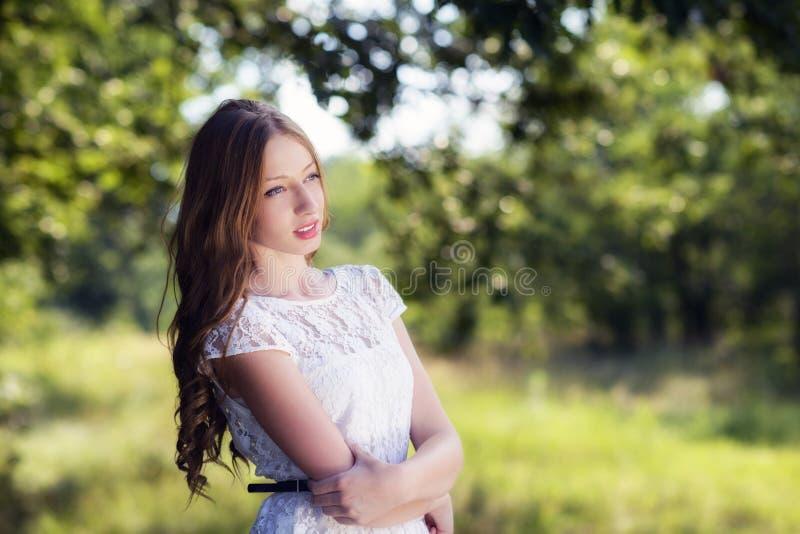 Den unga attraktiva kvinnan på sommargräsplan parkerar. arkivfoton