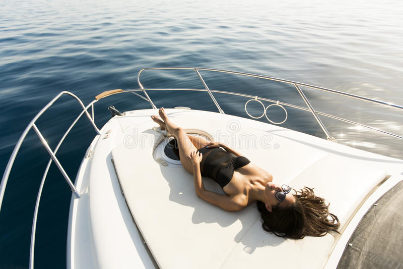 Den unga attraktiva kvinnan poserar på den lyxiga yachten som svävar på havet arkivfoton