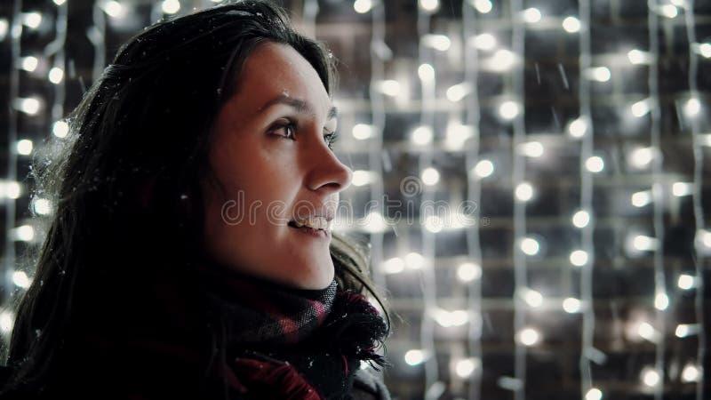Den unga attraktiva kvinnan som har gyckel, fångar den fallande snön för tungan på julnatten, ljus på bakgrund royaltyfri bild