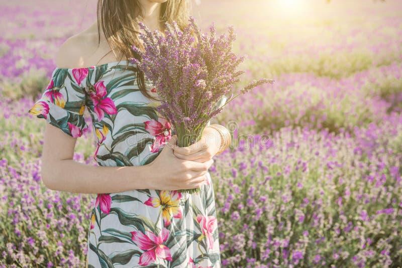 Den unga attraktiva kvinnan som rymmer en bukett av lavendel, blommar royaltyfri foto