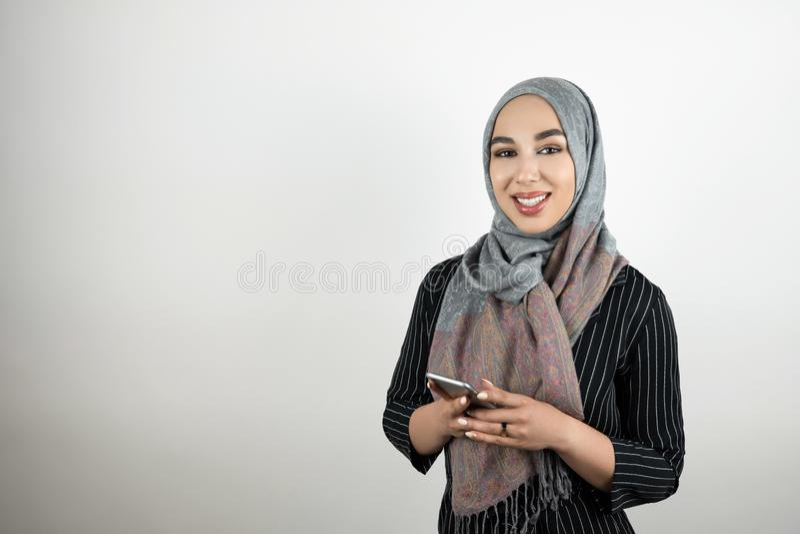 Den unga attraktiva le för turbanhijab för den muslimska kvinnan bärande smartphonen för innehavet för sjaletten i hennes händer  royaltyfria bilder