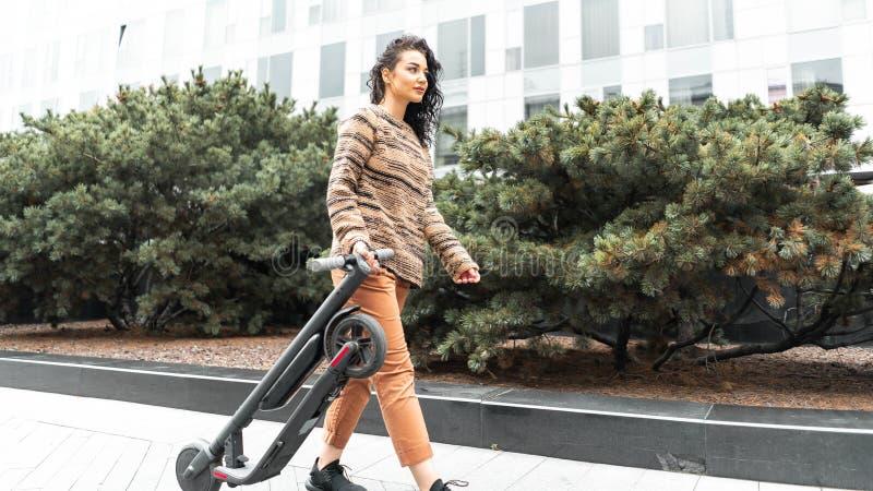 Den unga attraktiva le kvinnan som rymmer den elektriska sparksparkcykeln, medan gå för, går på gatan royaltyfri fotografi