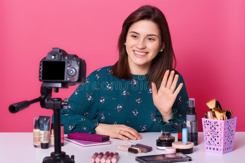 Den unga attraktiva livliga bloggeren stiger hennes hand, säger hälsningar till hennes tittare och att anteckna videoen för kanal royaltyfri fotografi