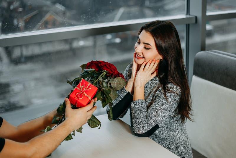 Den unga attraktiva lyckliga kvinnan fick den härliga buketten av röda rosor royaltyfria bilder