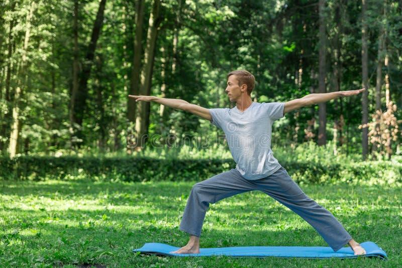 Den unga attraktiva mannen i en grå T-tröja och sweatpants som gör yogakrigaren, poserar i parkerar Han fördelade hans breda ben, royaltyfri foto