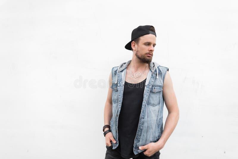 Den unga attraktiva mannen i en T-tröja i en grov bomullstvill tilldelar jeans i ett trendigt svart lock med ett skägg står royaltyfria bilder