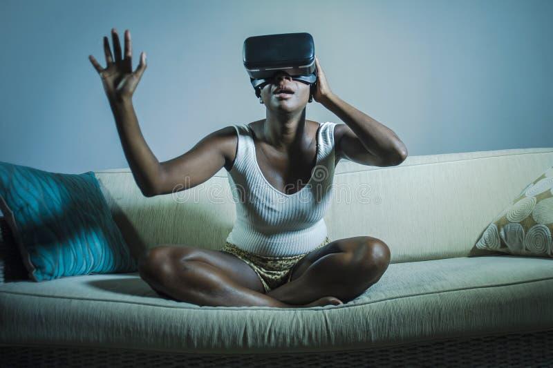 Den unga attraktiva nyfikna svarta afro amerikanska kvinnan som bär vision för VR 3d, rullar med ögonen tycka om fantastisk erfar royaltyfria foton