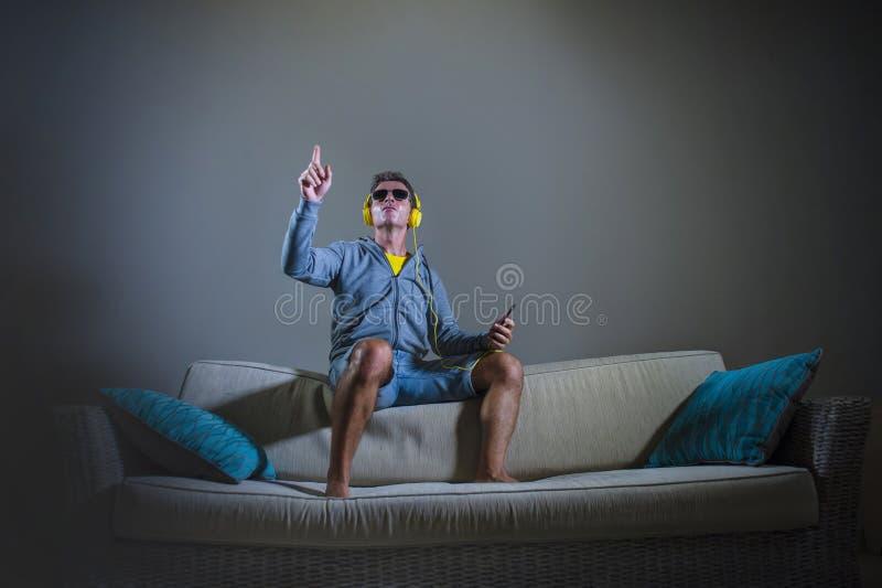 Den unga attraktiva och kalla lyckliga mannen som lyssnar till technomusik med gul hörlurar, hoppade överst av hem- inte för soff arkivfoton