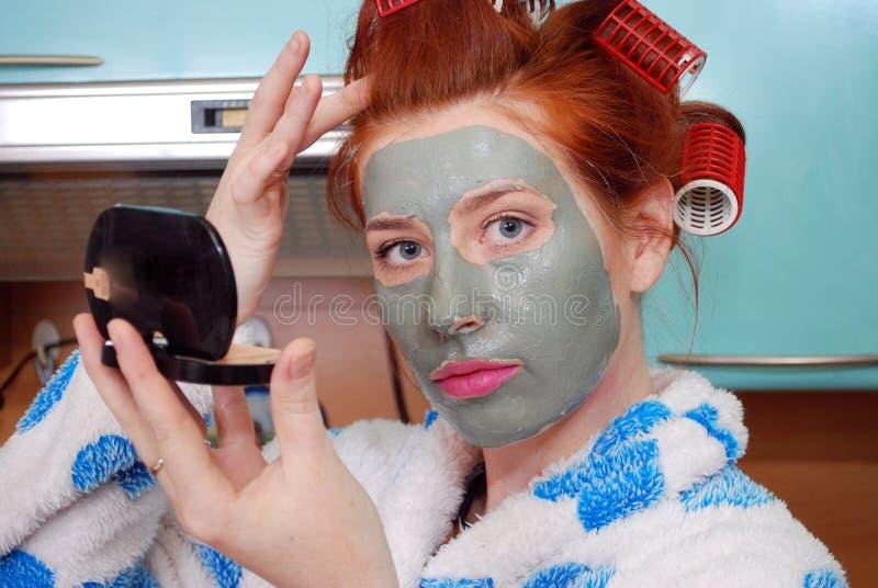 Den unga attraktiva röda flickan med en leraansiktsmask ser i en fick- spegel i kök royaltyfria bilder