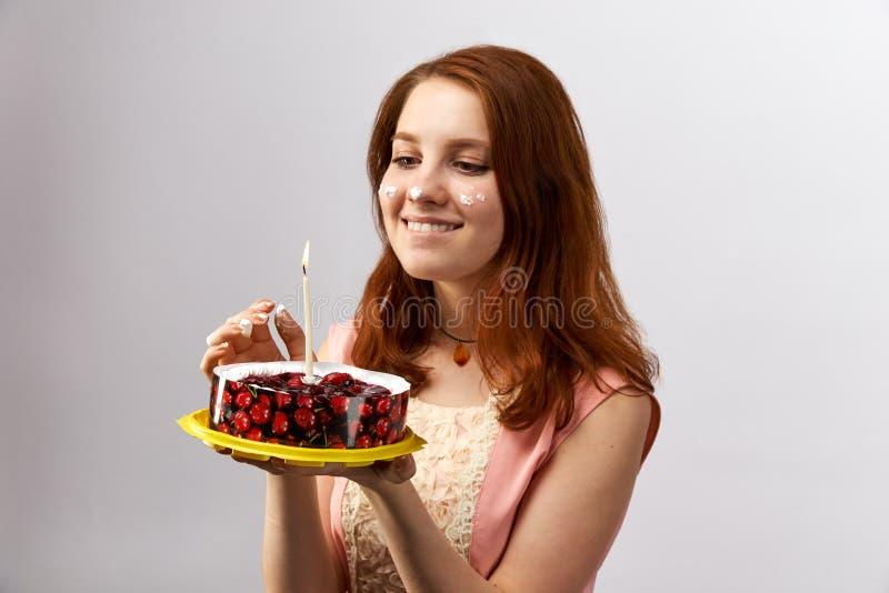 Den unga attraktiva rödhåriga flickan som rymmer en kaka med stearinljuset och, gör en önska på födelsedagen arkivfoton