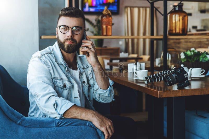 Den unga attraktiva skäggiga hipstermannen i moderiktiga exponeringsglas sitter i ett kafé under lunch som talar på en mobiltelef arkivfoton