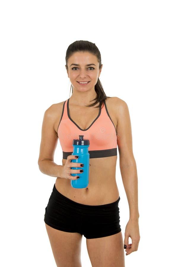 Den unga attraktiva sportkvinnan i kondition beklär att le lyckligt posera med vattenflaskan royaltyfria bilder
