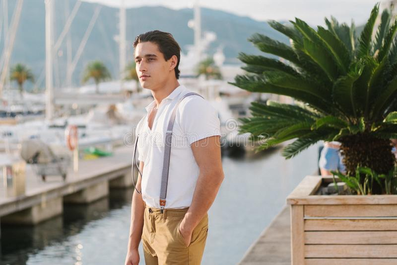 Den unga attraktiva stilfulla mannen promenerar pir med yachter och hotell Stående av den male modellen arkivbilder