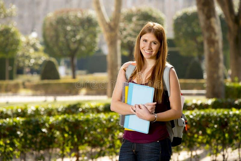 Den unga attraktiva studentflickan i universitetsområdegräsplan parkerar den bärande böcker och ryggsäcken arkivbilder