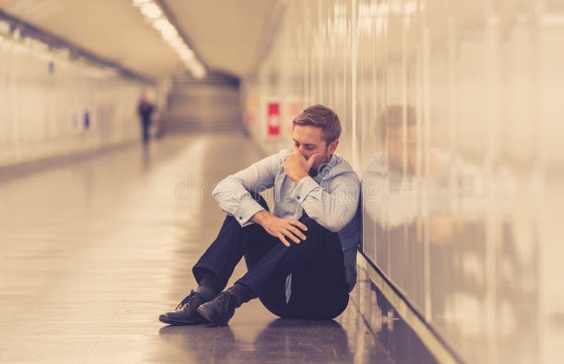 Den unga avfyrade affärsmannen förlorade i fördjupningen som gråter övergett sammanträde på jordlida för gångtunnel som var emoti royaltyfria bilder