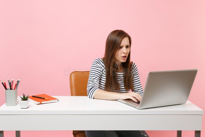 Den unga bekymrade kvinnan har problemet som arbetar på projekt, medan sitta på kontoret med den isolerade PCbärbara datorn på pa arkivbild