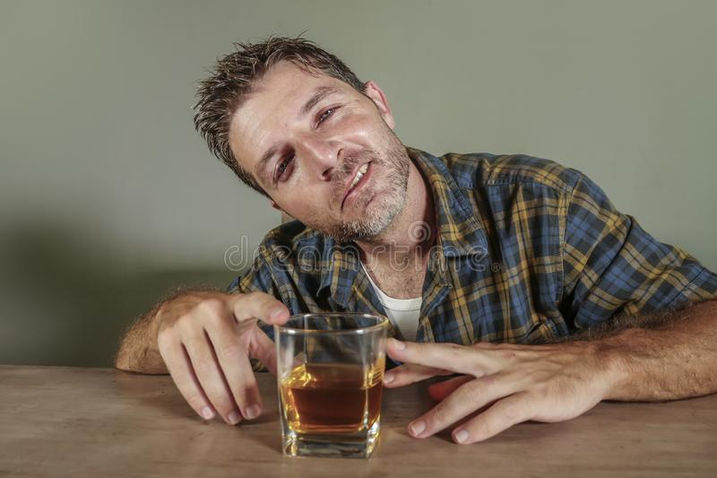 Den unga berusade och förbannade alkoholiserade mannen slöde bort att dricka whiskyexponeringsglas som berusades och som var smut royaltyfria bilder