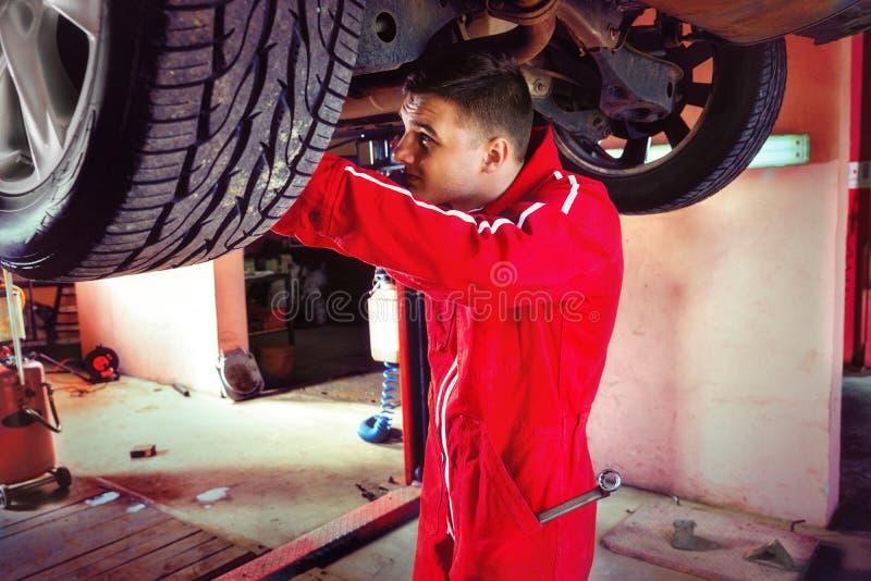 Den unga bilmekanikern i likformig reparerar hjulet, medan arbeta u royaltyfria bilder