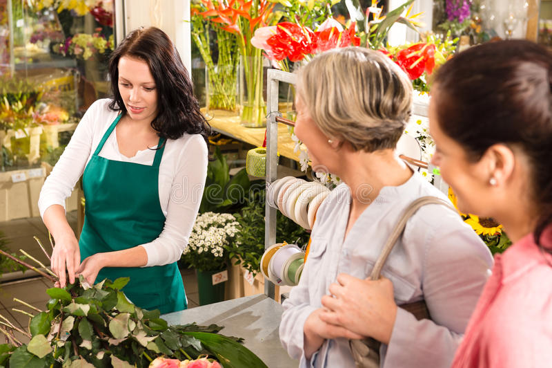 Den unga blomsterhandlaren som förbereder klippta blommor, shoppar köparear arkivfoto