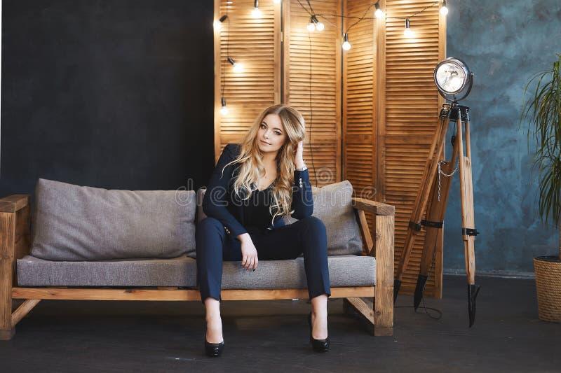 Den unga blonda affärsdamen i blåttdräkt sitter på träsoffan i modern inre royaltyfri fotografi
