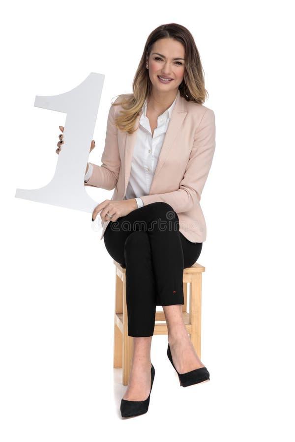 Den unga blonda affärskvinnan rymmer tecknet för nummer ett, medan sitta fotografering för bildbyråer