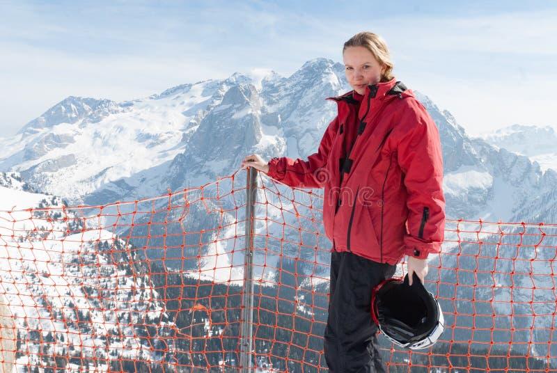 Den unga blonda Caucasian kvinnaflickan som poserar i fjällängberg med, skidar utrustning arkivfoto