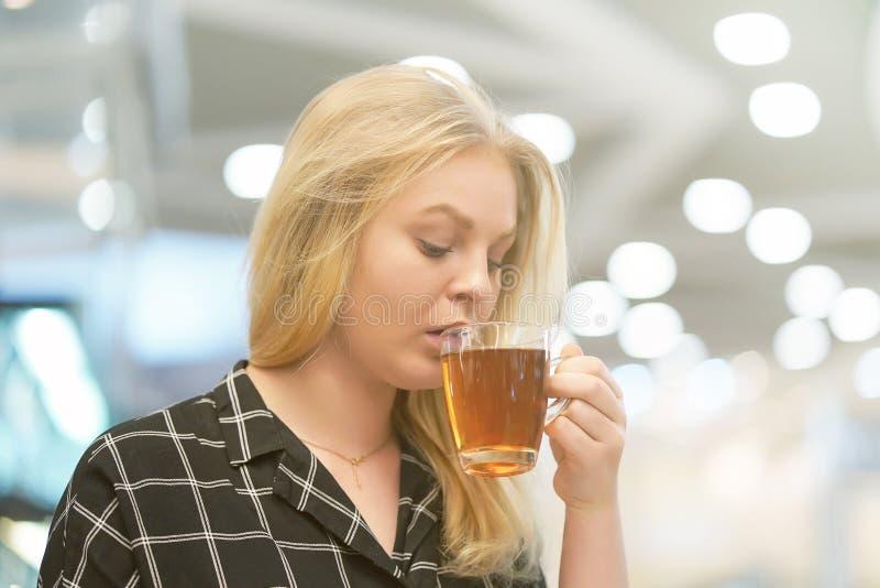 Den unga blonda flickan dricker te i ett kafé royaltyfri fotografi