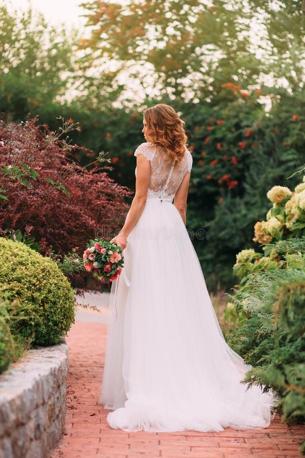 Den unga blonda flickan i en elegant lång vit gifta sig ljusklänning med ett långt drev står tillbaka till kameran i a arkivbild