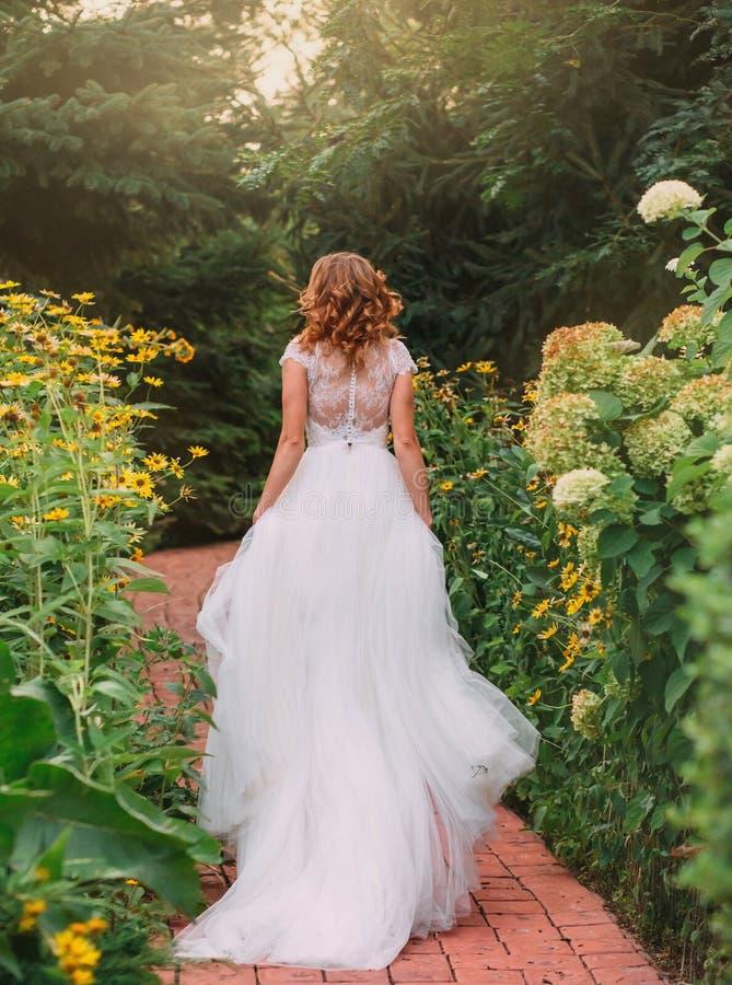 Den unga blonda flickan i en elegant lång vit gifta sig ljusklänning med ett långt drev står tillbaka till kameran i a royaltyfri bild